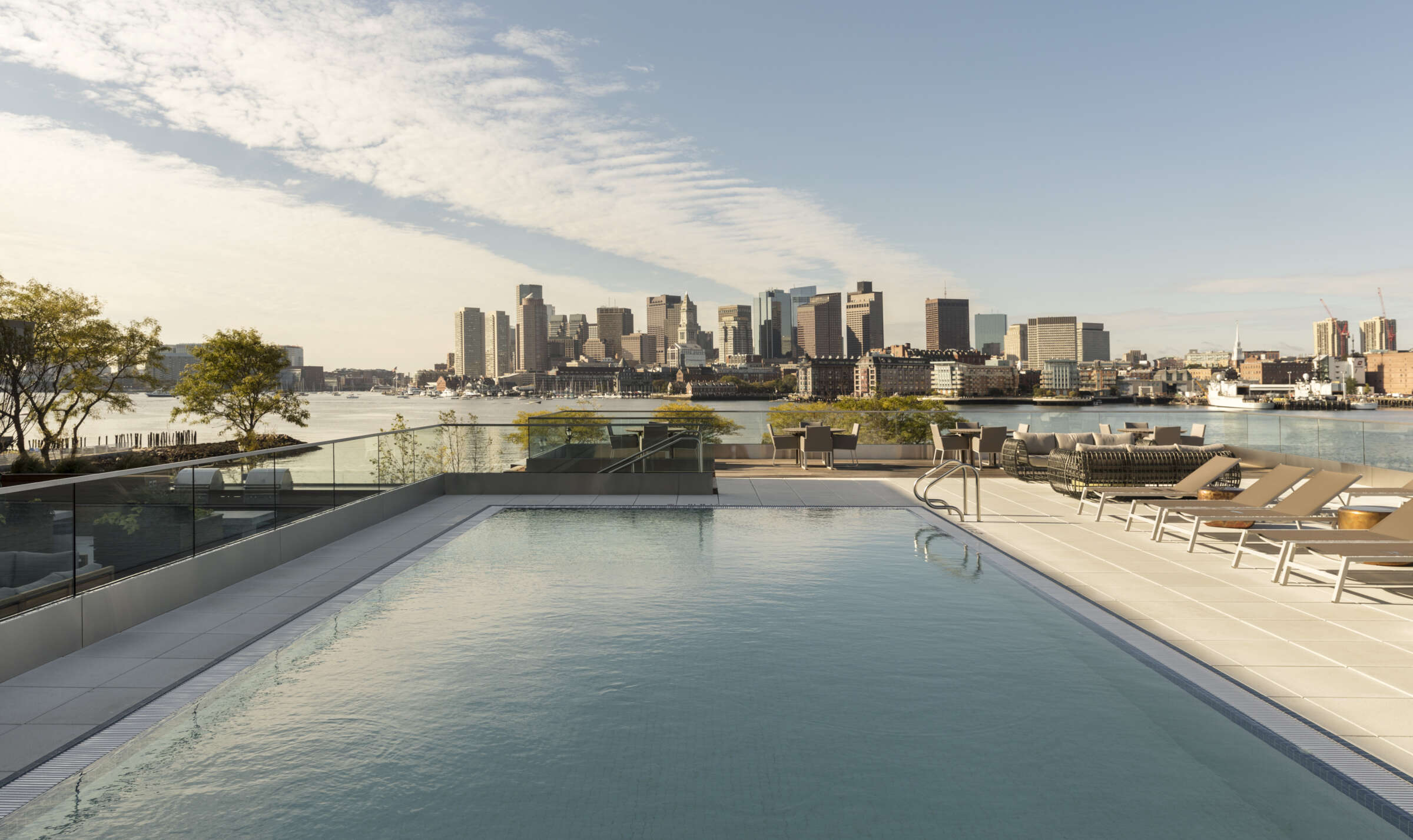The Eddy rooftop pool and lounge chairs with views of Boston