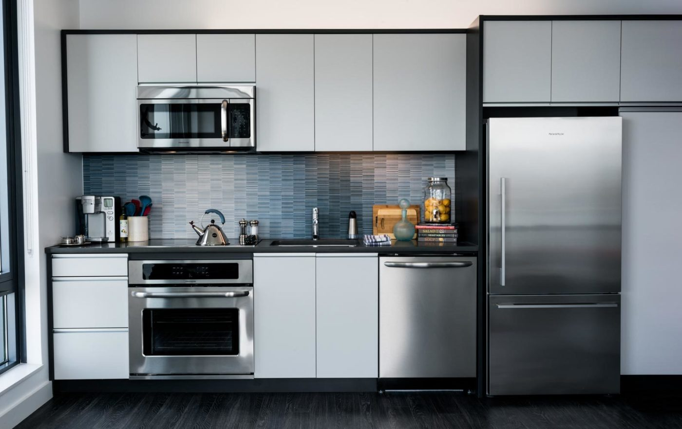 Eddy East Boston apartment kitchen with stainless steel appliances and white cabinets
